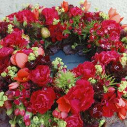 Blütentrauerkranz mit roten Nelken